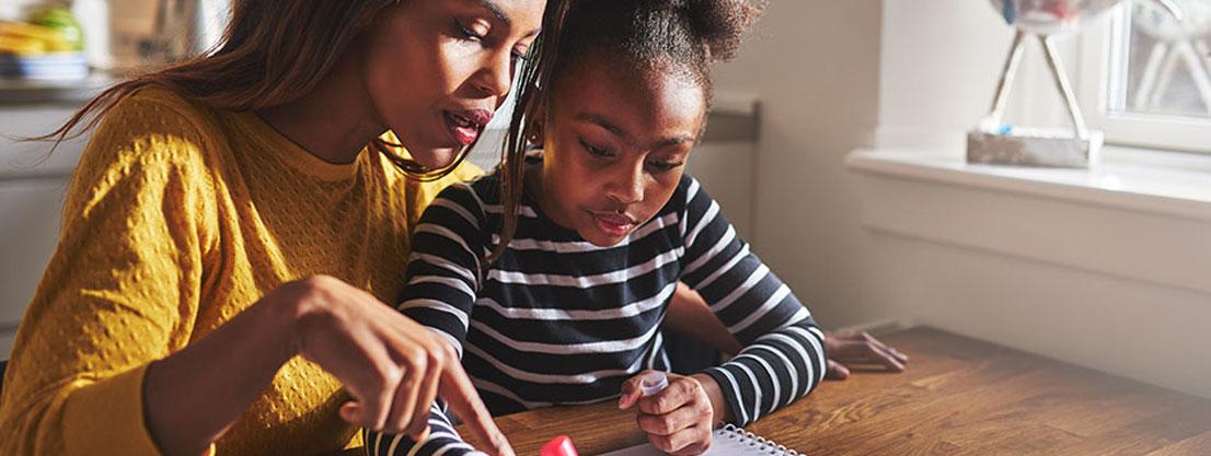 Mutter unterstützt Kind bei Aufgaben