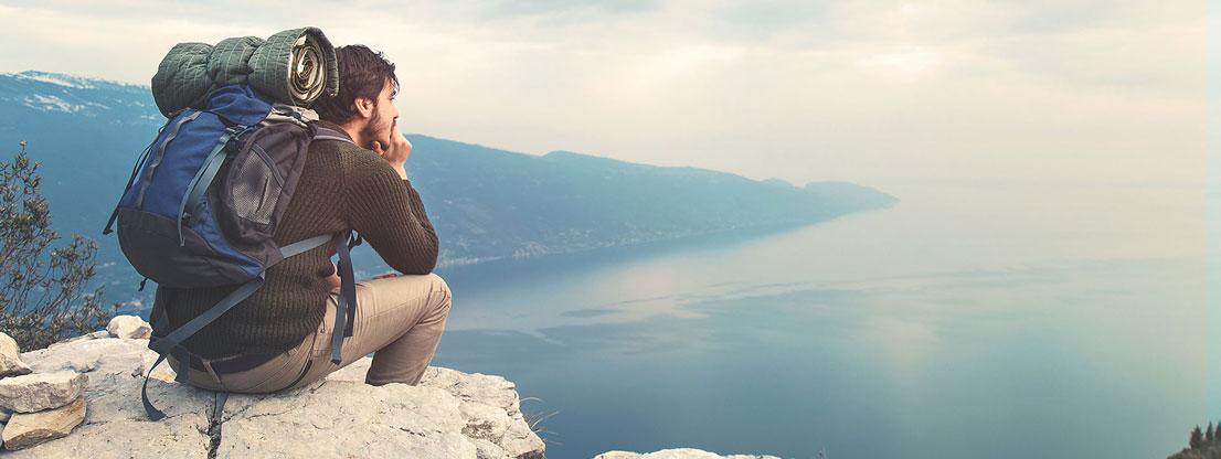 Mann sitzt auf Felsen und lässt seinen Gedanken Raum