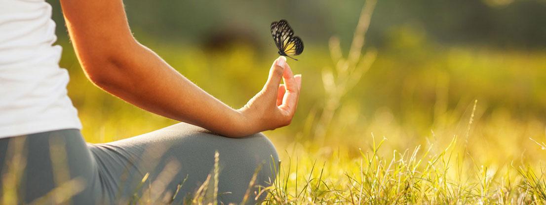 Frau meditiert mit Schmetterling
