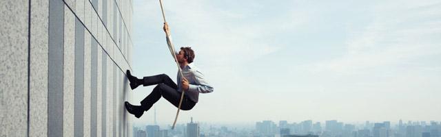 Mann klettert an Hauswand in großer Höhe