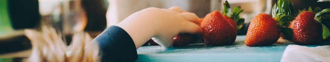 Kind greift nach Erdbeeren