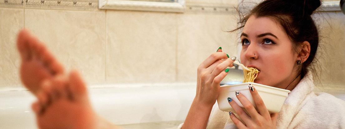 Frau isst Fast Food in der Badewanne