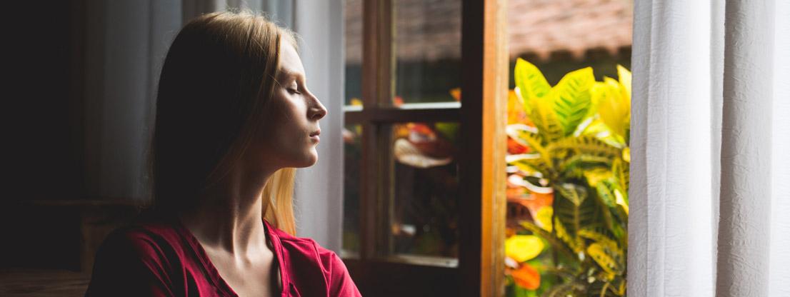 Woman at window, mindfulness