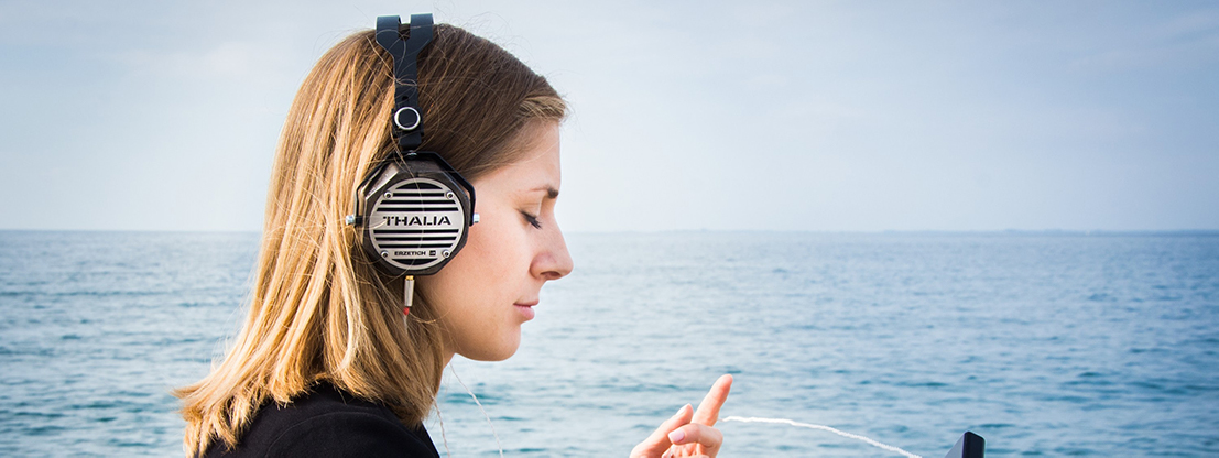 Woman with headphones by the sea, music and binaural beats