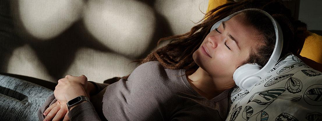 Woman sleeping, headphones with binaural beats